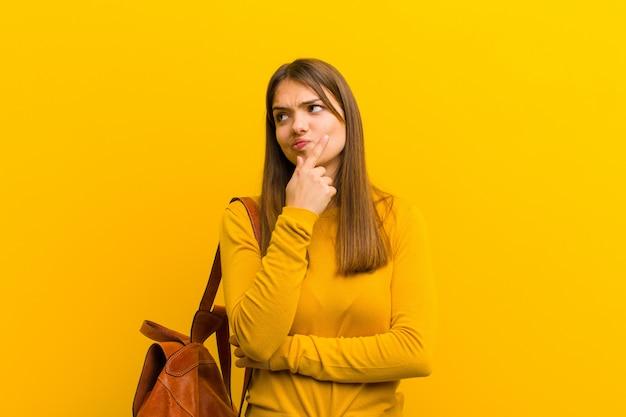 Młoda piękna kobieta myśli, czując się niepewnie i zdezorientowana, z różnymi opcjami, zastanawiając się, jaką decyzję podjąć pod pomarańczową ścianą