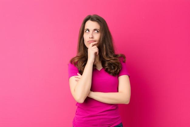 Młoda piękna kobieta myśli, czując się niepewnie i zdezorientowana, z różnymi opcjami, zastanawiając się, jaką decyzję podjąć przeciwko różowej ścianie