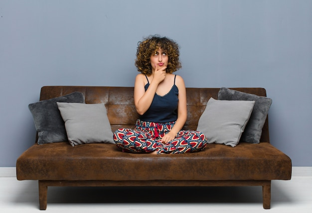 Młoda piękna kobieta myśli, czując się niepewnie i zdezorientowana, z różnymi opcjami, zastanawiając się, którą decyzję podjąć, siedząc na kanapie.