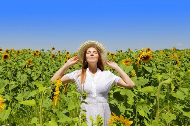 Młoda piękna kobieta na kwitnącym słonecznika polu w lecie