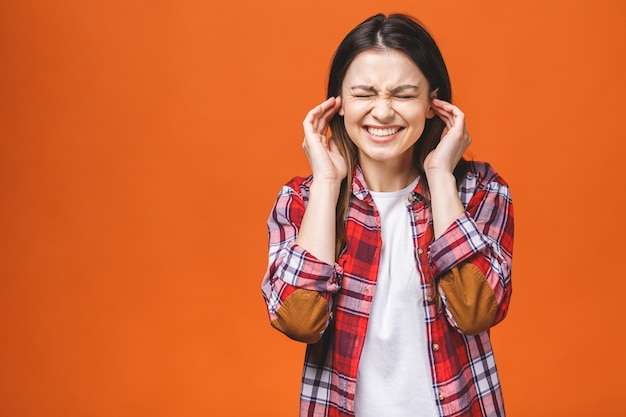 Młoda piękna kobieta na odosobnionym pomarańczowym tle cierpi na ból głowy zdesperowany i zestresowany z powodu bólu i migreny. ręce na głowę.
