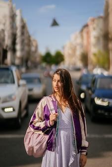 Młoda piękna kobieta na tle samochodów