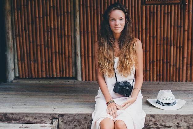 Młoda piękna kobieta na tropikalnych wakacjach w azji, styl lato, biała sukienka boho, trampki, aparat cyfrowy, podróżnik, słomkowy kapelusz, uśmiechnięta, boho