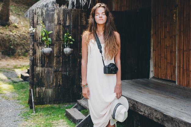 Młoda piękna kobieta na tropikalnych wakacjach w azji, styl letni, biała sukienka boho, trampki, aparat cyfrowy, podróżnik, słomkowy kapelusz, zrelaksowany,
