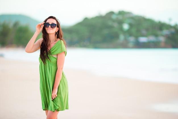 Młoda piękna kobieta na tropikalnym wybrzeżu. szczęśliwa dziewczyna relaksuje przy białego piaska tropikalną plażą