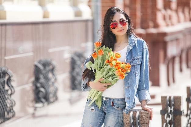 Młoda piękna kobieta na zewnątrz w okresie wiosennym. atrakcyjny dziewczyny zakończenie w górę portreta. dama trzyma prezenty, przedstawia pudełka. kobieta z kwiatami. wesoły żeński gospodarstwa tulipany.