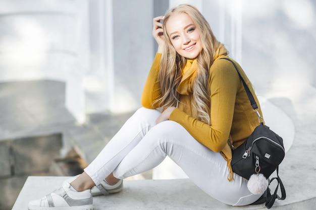 Młoda piękna kobieta na zewnątrz. zbliżenie portret rozochocony ladyon wiosny lub jesieni tło. dziewczyna z plecakiem.