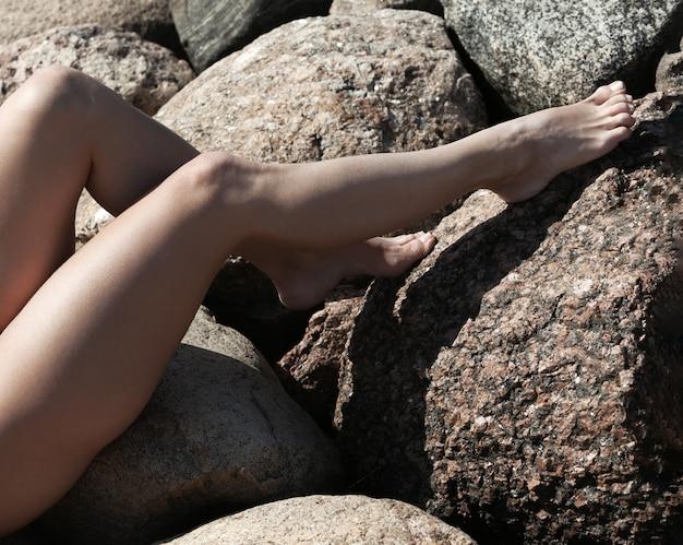 Młoda piękna kobieta nago pozowanie na kamiennym falochronie. naga brunetka ciesząca się naturą
