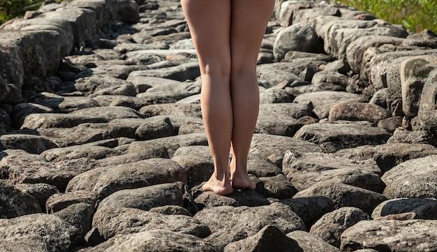 Młoda piękna kobieta nago pozowanie na kamiennym falochronie.
