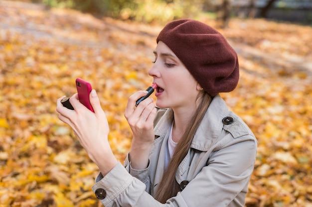 Młoda piękna kobieta nałożyła szminkę i patrząc w lustro na tle jesień park.