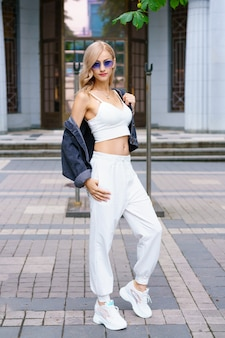 Młoda piękna kobieta narodowości kakaz pozuje po południu na ulicy miasta w białym dresie i niebieskich dżinsach pewna siebie blondynka w okularach przeciwsłonecznych latem