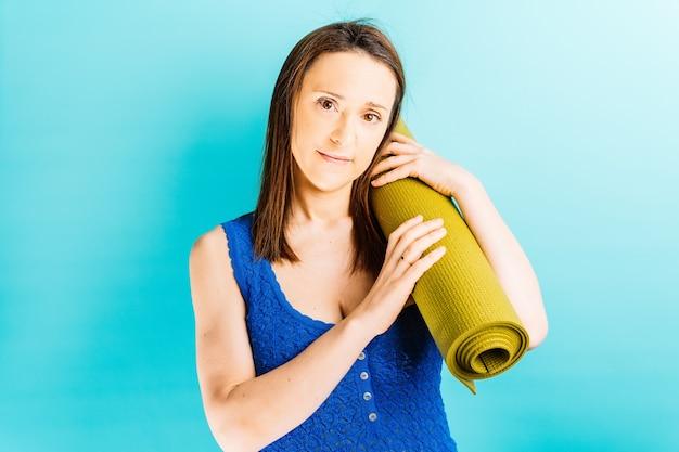 Młoda piękna kobieta niosąca matę do jogi na ramieniu z niebieskim tłem zdrowe życie joga