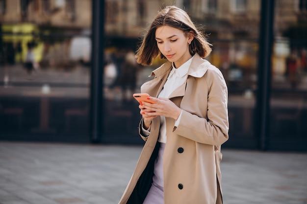 Młoda piękna kobieta nosi płaszcz spaceru po mieście i rozmawia przez telefon