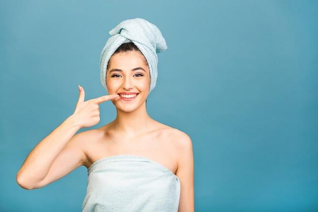 Młoda piękna kobieta nosi ręcznik po kąpieli stojącej na na białym tle niebieskim tle