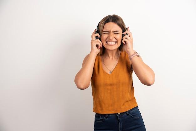 Młoda piękna kobieta nosi słuchawki na białym tle.