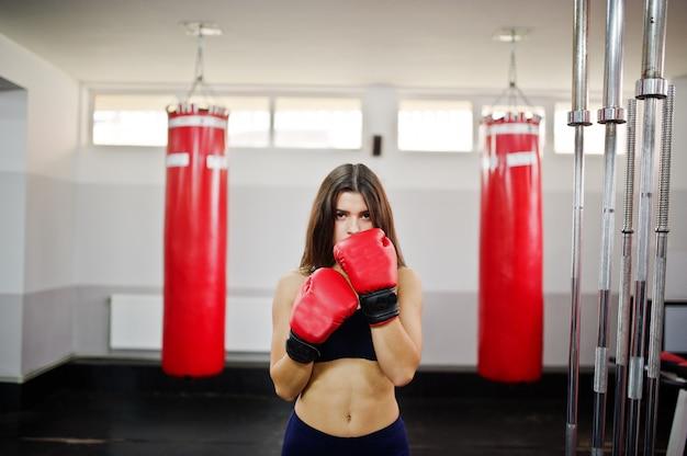 Młoda piękna kobieta, nosić na rękawice bokserskie, wykonując ćwiczenia i ciężko pracując w siłowni