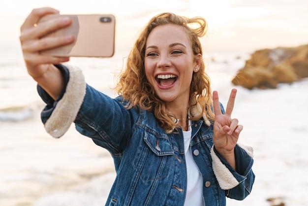 Młoda piękna kobieta o blond kręconych włosach, korzystająca ze smartfona podczas spaceru nad morzem