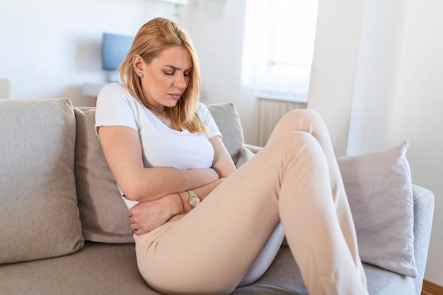 Młoda piękna kobieta o bolesny ból brzucha. kobieta z bólem menstruacyjnym trzyma bolący brzuch - koncepcja bólu ciała. kobieta mająca ból brzucha, rozstrój żołądka lub skurcze menstruacyjne.