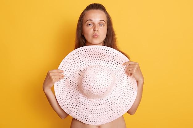 Młoda piękna kobieta o ciemnych włosach bez ubrania, chowa się za dużym słomkowym kapeluszem odizolowanym na żółtej ścianie, trzymając usta zaokrąglone, jakby pokazywał gest pocałunku.