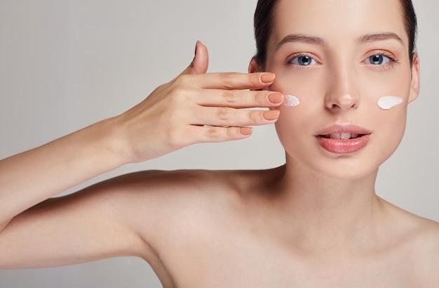 Młoda piękna kobieta o niebieskich oczach i brązowych włosach prawą ręką rozmazuje krem kosmetyczny na twarzy. krem na policzkach. ochrona skóry.