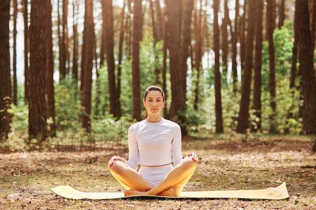 Młoda piękna kobieta o przyjemnym wyglądzie siedzi na karemacie w pozie jogi