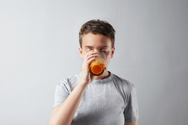 Młoda piękna kobieta o zdrowo doskonałej skórze marzycielsko pije swój świeży organiczny sok pomarańczowy z marchwi