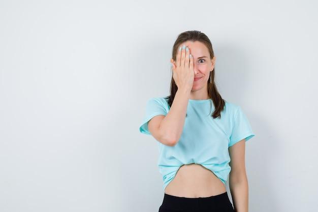 Młoda piękna kobieta obejmujące oko ręką w t-shirt i patrząc radosny. przedni widok.