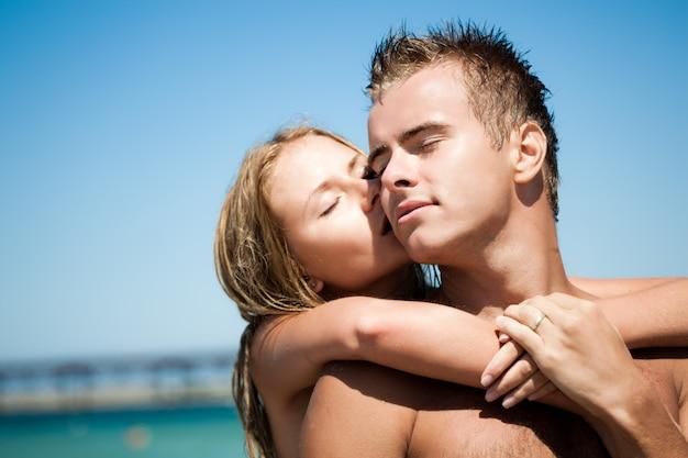 Młoda piękna kobieta obejmuje i całuje od plecy jej uśmiechniętego chłopaka z błękitnym morzem i piaskowatą plażą przy tłem