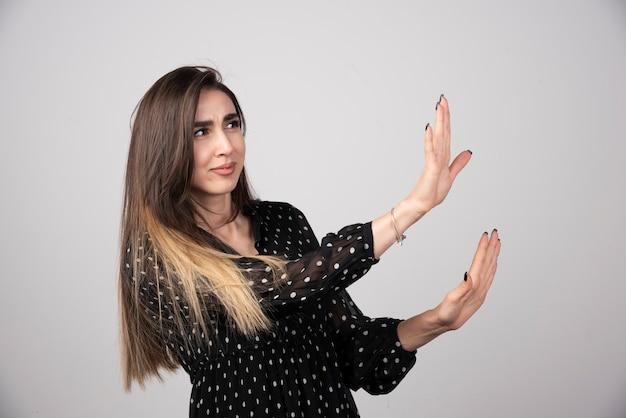 Młoda piękna kobieta oddala ręce dłonie pokazujące odmowę i zaprzeczenie.