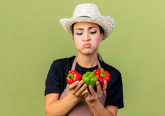 Młoda piękna kobieta ogrodniczka w fartuchu i kapeluszu trzymająca kolorowe papryki patrząc na nich ze smutnym wyrazem dmuchania w policzki stojąc nad jasnozieloną ścianą