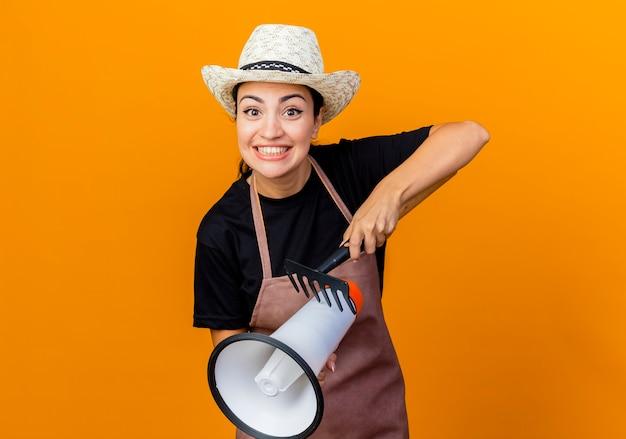 Młoda piękna kobieta ogrodniczka w fartuchu i kapeluszu trzymająca mini grabie i megafon patrząc na przód uśmiechnięta wesoło stojąc nad pomarańczową ścianą