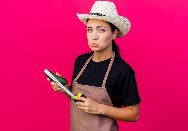 Młoda piękna kobieta ogrodnik w fartuch i kapelusz gospodarstwa bakłażan i taśma miernicza patrząc z przodu ze smutnym wyrazem stojącym nad różową ścianą