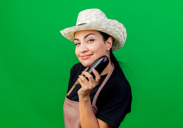 Młoda piękna kobieta ogrodnik w fartuch i kapelusz gospodarstwa bakłażan, patrząc na przód, uśmiechając się chytrze stojąc na zielonej ścianie