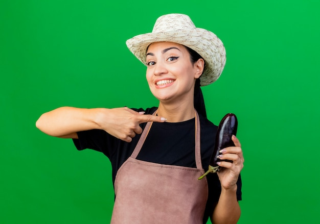 Młoda piękna kobieta ogrodnik w fartuch i kapelusz gospodarstwa bakłażan, wskazując palcem wskazującym na to uśmiechnięty stojący nad zieloną ścianą
