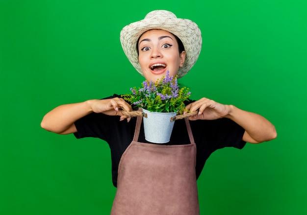 Młoda piękna kobieta ogrodnik w fartuch i kapelusz gospodarstwa roślina doniczkowa, uśmiechając się radośnie