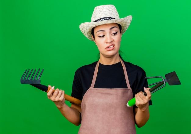 Młoda piękna kobieta ogrodnik w fartuch i kapelusz gospodarstwa sprzęt ogrodniczy patrząc zdezorientowany próbuje dokonać wyboru