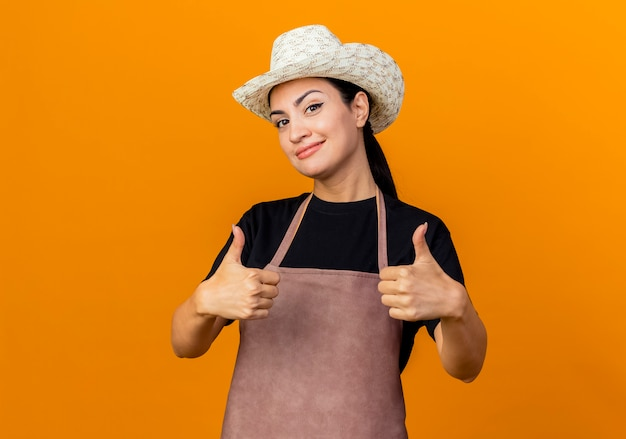 Młoda piękna kobieta ogrodnik w fartuch i kapelusz patrząc na przód uśmiechnięty pokazując kciuki stojąc nad pomarańczową ścianą