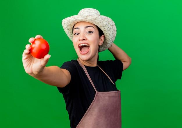 Młoda piękna kobieta ogrodnik w fartuch i kapelusz pokazując pomidor szczęśliwy i podekscytowany stojąc nad zieloną ścianą