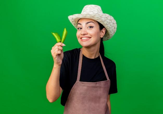 Młoda piękna kobieta ogrodnik w fartuch i kapelusz pokazując złamaną zieloną paprykę chili, patrząc na przód uśmiechnięty z szczęśliwą twarzą stojącą nad zieloną ścianą