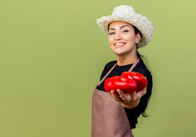 Młoda piękna kobieta ogrodnik w fartuch i kapelusz pokazuje czerwoną paprykę patrząc na przód uśmiechnięty wesoło stojąc nad jasnozieloną ścianą