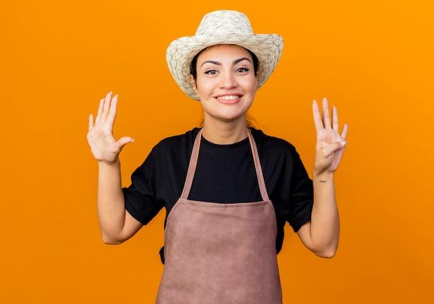 Młoda piękna kobieta ogrodnik w fartuch i kapelusz pokazuje i wskazuje palcami numer dziewięć uśmiechnięty stojący nad pomarańczową ścianą