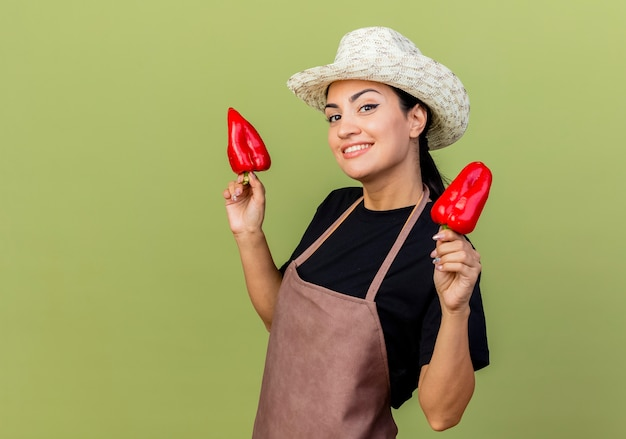 Młoda piękna kobieta ogrodnik w fartuch i kapelusz trzymając czerwoną paprykę patrząc na przód uśmiechnięty wesoło stojąc nad jasnozieloną ścianą