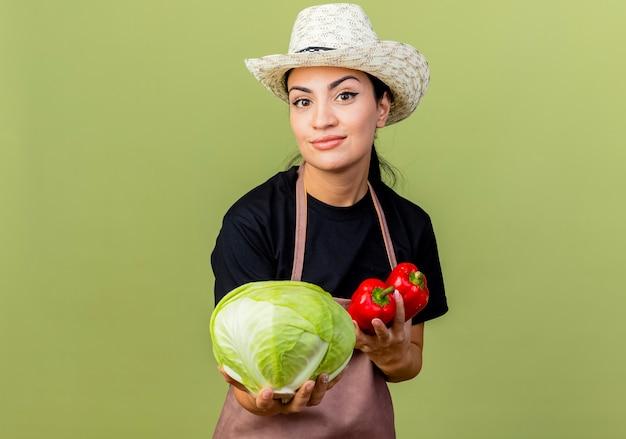 Młoda piękna kobieta ogrodnik w fartuch i kapelusz, trzymając kapustę i czerwoną paprykę uśmiechnięty stojący nad jasnozieloną ścianą