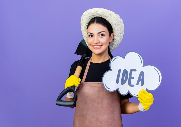 Młoda piękna kobieta ogrodnik w fartuch i kapelusz, trzymając łopatę i znak bańki z pomysłem słowo uśmiechając się pewnie stojąc nad niebieską ścianą