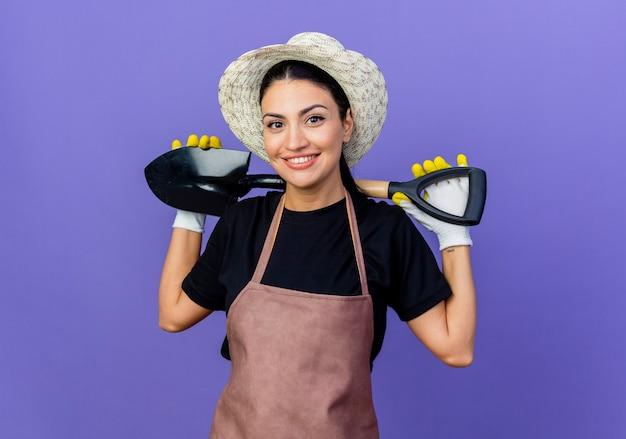 Młoda piękna kobieta ogrodnik w fartuch i kapelusz trzymając łopatę patrząc z przodu z uśmiechem na twarzy stojącej nad niebieską ścianą
