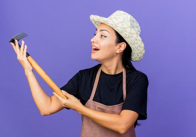 Młoda piękna kobieta ogrodnik w fartuch i kapelusz trzymając mini prowizji patrząc na to uśmiechnięty wesoło stojąc na niebieskiej ścianie