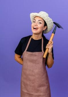 Młoda piękna kobieta ogrodnik w fartuch i kapelusz trzymając mini prowizji, uśmiechając się z szczęśliwą twarzą stojącą nad niebieską ścianą