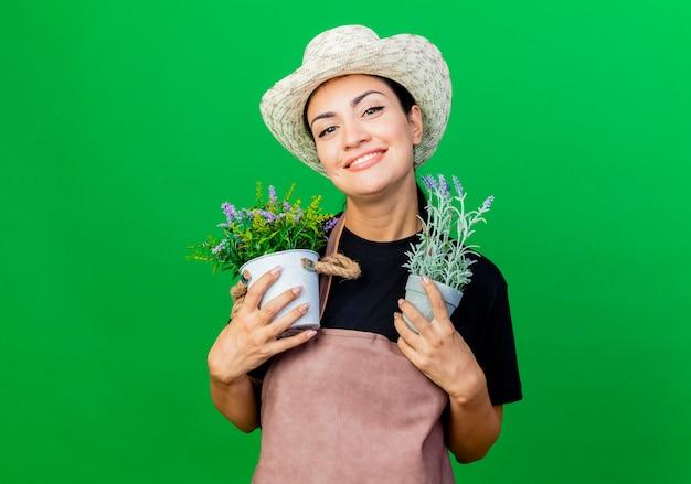 Młoda piękna kobieta ogrodnik w fartuch i kapelusz, trzymając rośliny doniczkowe, uśmiechając się z radosną buźkę