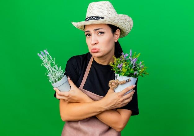 Młoda piękna kobieta ogrodnik w fartuch i kapelusz, trzymając rośliny doniczkowe ze smutnym wyrazem