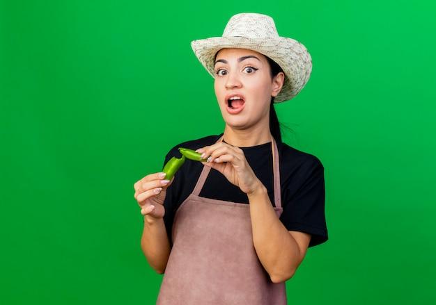 Młoda piękna kobieta ogrodnik w fartuch i kapelusz, trzymając złamaną zieloną paprykę chili, patrząc niezadowolony stojąc na zielonej ścianie